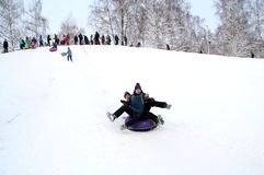 Two boys riding on one sled. Winter fun. The action takes place on the outskirts of the city of Monino. Residents of the town come with children on a snow hill royalty free stock photos