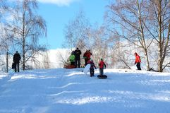 Children raise the sled up the hill. Winter fun. The action takes place on the outskirts of the city of Monino. Residents of the town come with children on a stock images