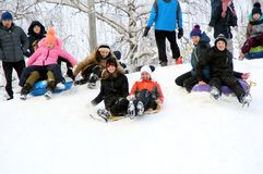 Children gather a crowd to move down the hill. Winter fun. The action takes place on the outskirts of the city of Monino. Residents of the town come with stock photos
