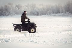 Winter fun on the ATV. A fisherman rides on the frozen lake in winter quartro bike on the background of beautiful winter landscape with snow-covered trees in Royalty Free Stock Image