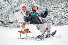 Winter fun, boy and a girl sledding at winter time Stock Photo