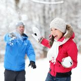 Winter fun - couple in snowball fight. Having fun together in forest snow landscape. Happy young interracial couple playing together in the snow royalty free stock image