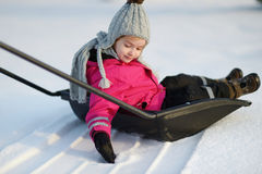 Winter fun: a girl having a ride on a snow shovel Stock Image