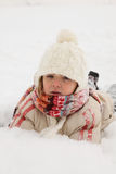 Winter Fun - Girl lying on snow Royalty Free Stock Images