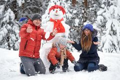 Winter fun. a girl, a man and a boy making a snowman. royalty free stock image
