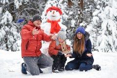 Winter fun. a girl, a man and a boy making a snowman. Stock Photo