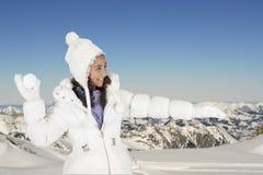 Winter fun, girl throwing a snow ball Royalty Free Stock Image