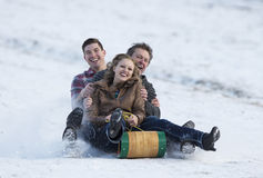 Winter Fun. Happy adult family enjoying some winter fun on a toboggan Stock Images