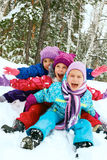 Winter fun, happy children sledding at winter time. Winter fun, snow, happy children sledding at winter time Royalty Free Stock Images