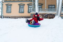 Winter fun. happy girl riding sled from the mountain royalty free stock photos
