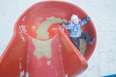 Winter fun of little girl on red plastic playground slide Stock Photo
