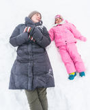 Winter fun. A mother and child lying in snow, having fun during winter season Stock Images