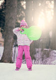 Winter fun with a sled. Portrait of a little girl holding green plastic sled in the park in winter Stock Images