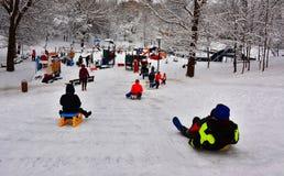 Winter Fun - Sledding. Children sledding in a park full of snow Royalty Free Stock Images