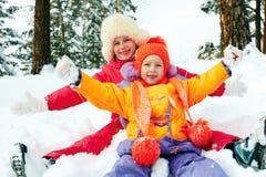 Winter fun, snow, happy children sledding at winter time Royalty Free Stock Photos