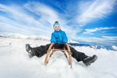 Winter fun in snow mountains boy on sledge. Little boy in blue coat slide on sledge from the hill with legs first Stock Photography