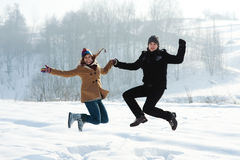 Winter fun, young couple jumping outdoors. Winter collection: winter fun, young couple jumping outdoors Royalty Free Stock Images