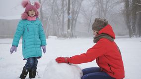 Winter games. Two sisters make a snowman in the winter outdoors. Older and younger sisters with fun make a snowman in the street stock footage