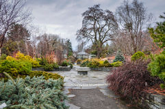 Winter Garden. Central mill, stone, conifers, and evergreens in a Winter Garden at Cornell University in Ithaca, New York Royalty Free Stock Images
