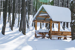 Winter gazebo in the woods. Winter wooden gazebo in a snowy forest, the concept of winter Royalty Free Stock Photos