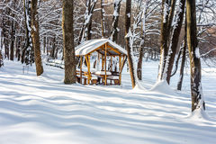 Winter gazebo in the woods. Winter wooden gazebo in a snowy forest, the concept of winter Stock Images