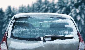 Winter gefrorenes hinteres Autofenster, einfrierendes Eisglas der Beschaffenheit mit Schnee über schneebedecktem Stockfotos