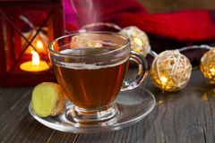 Winter ginger tea cup with candle lantern and lights Royalty Free Stock Photos