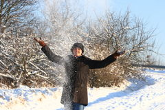 Winter Girl. Girl in snow is throwing white powder snow into the blue sky. She is wearing a nice hat Royalty Free Stock Image