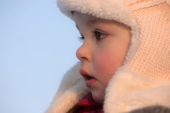 Winter girl. A child wearing a fur cap in a cold winter day Royalty Free Stock Photos