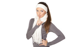 Winter girl asking for silence. Young winter woman with finger on lips over white background Stock Image