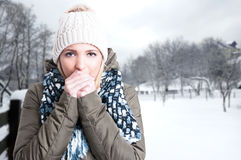 Winter girl blowing on her hands Royalty Free Stock Photos