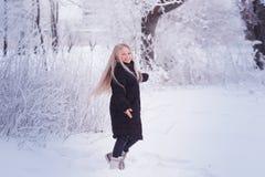 Winter girl blowing snow. Beauty Joyful Teenage Model Girl having fun in winter park. Beautiful girl laughing outdoors. Enjoying n Royalty Free Stock Images
