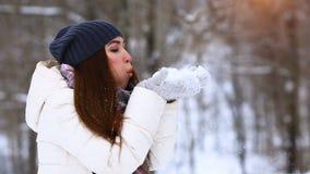 Winter girl blowing snow. Beauty Joyful Teenage Model Girl having fun in winter park. Beautiful young woman laughing outdoors. Enj stock footage