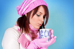 Winter girl blows her tea Stock Images