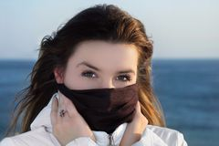 The Winter Girl the Brunette. The winter girl covers with a scarf the beautiful face from a frosty winter wind Stock Image