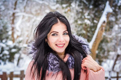 Winter. Girl brunette capless smiles on the background of snow Royalty Free Stock Photography