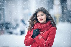 Winter. Girl brunette capless smiles on the background of snow. Close-up. hair develops. Wind and snow Royalty Free Stock Image