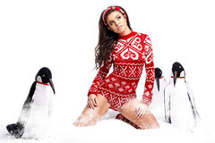 Winter Girl in dress holding a large toy penquin. Stock Photos