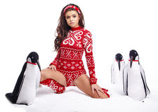 Winter Girl in dress holding a large toy penquin. Stock Photo