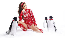 Winter Girl in dress holding a large toy penquin. Stock Images