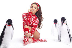 Winter Girl in dress holding a large toy penquin. Royalty Free Stock Photos