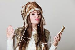 Winter girl enjoying music. Royalty Free Stock Photography