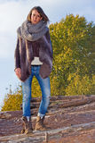 Winter girl with fur. Stunning woman wearing winter outfit with fur, standing on tree logs Royalty Free Stock Images