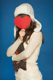 Winter girl holding heart shape in front of face Stock Photo