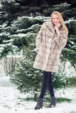 Winter Girl in Luxury Fur Coat. On the background of fir trees Royalty Free Stock Photos
