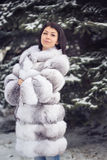 Winter Girl in Luxury Fur Coat. On the background of fir trees Stock Photography