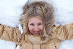 Winter girl is lying on snow Stock Photography