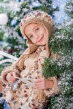 Winter girl. Girl peeking out from behind tree Stock Photo