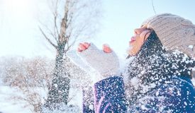 Winter girl portrait. Beauty joyful model girl blowing snow, having fun in winter park. Beautiful young woman enjoying nature stock photo
