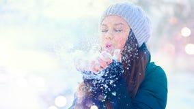 Winter girl portrait. Beauty joyful model girl blowing snow, having fun in winter park. Beautiful young woman enjoying nature royalty free stock photos